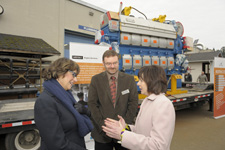Minister Yelich (L) chats with Camosun College's Kathryn Laurin and Dr. Tom Roemer in front of a ship engine donated for student training purposes.