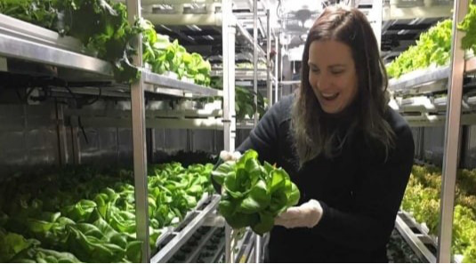 Woman holding head of lettuce grown in Churchill, Manitoba
